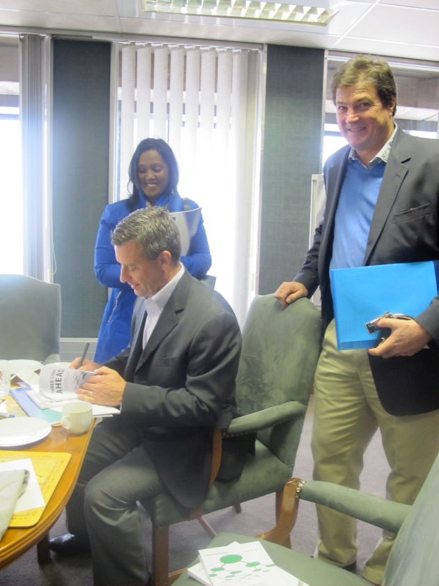 David Silverstein signs books for Intel's SA Country Manager Videsha Proothveerajh and Charles Bromley, CEO of PG Glass.